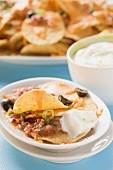 Tortilla chips with melted cheese, olives and sour cream