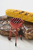 Grilled beef steak with corn on the cob, toy barbecue