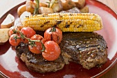 Grilled steak with corn on the cob, cherry tomatoes, potatoes