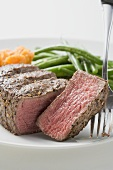 Beef steak, a slice cut off, with vegetables