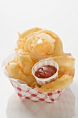 Deep-fried onion rings with ketchup in cardboard container