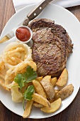 Rib-eye steak with onion rings, ketchup and potato wedges