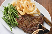 Rib-eye steak with green beans and deep-fried onion rings