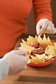Hands dipping nachos in tomato salsa