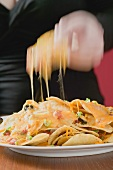 Hand taking tortilla chip with melted cheese from plate