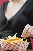Woman reaching for nachos in cardboard container