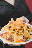 Woman holding plate of nachos with melted cheese