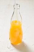 Orange juice in bottle with straw