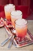Three fruity drinks with orange juice & pomegranate