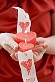 Hands holding two heart-shaped candles on ribbon