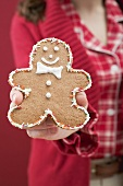 Woman holding decorated gingerbread man