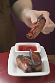 Woman holding glazed pork rib over chilli sauce