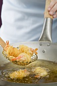 Deep-frying noodle-wrapped prawns in wok