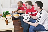Three football fans with nibbles and beer watching TV