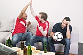 Three football fans, disappointed and excited, watching TV