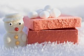 Small marzipan snowman and box in snow