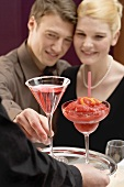 Waiter serving two drinks to romantic couple