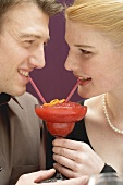Romantic couple drinking Strawberry Daiquiri out of one glass
