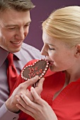 Woman tasting chocolate heart with the words Be Mine