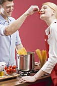 Couple cooking spaghetti with tomatoes