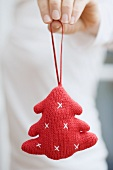 Hand holding knitted Christmas tree ornament