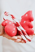 Hands holding Christmas tree ornaments