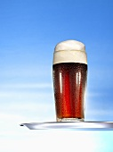Glass of malt beer on tray
