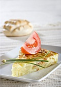 Potato tortilla with chives and wedge of tomato