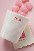 Pink heart-shaped sweets, beaker and Valentine card