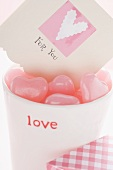Pink heart-shaped sweets & card in beaker for Valentine's Day