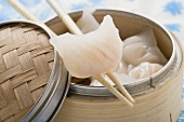 Dim sum in bamboo steamer and on chopsticks (Asia)