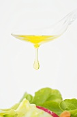 Olive oil dripping from a spoon onto salad