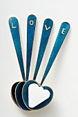 Heart-shaped spoons with sugar lump and the word LOVE