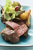 Beef fillet steak with potato wedges and salad