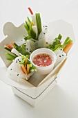 Reispapierröllchen mit Gemüse und Sauce im Take-Out-Behälter
