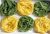 Green and yellow ribbon pasta nests (overhead view)