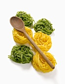 Green and yellow ribbon pasta nests with wooden spoon