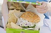 Woman holding lunch box containing chicken sandwich & crisps