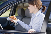 Young woman with croissant in her hand getting into car