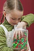 Small girl reaching into jar of chocolate beans