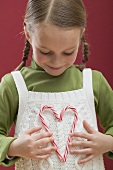 Small girl holding heart made from two candy canes