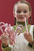 Small girl holding glass full of candy canes