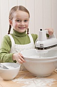Small girl using electric mixer
