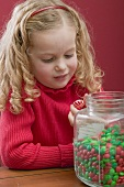 Small girl holding peppermint, jar of chocolate beans