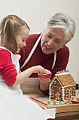 Small girl with grandmother decorating gingerbread house