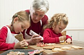 Grandmother & two granddaughters decorating Christmas biscuits