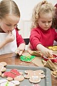 Two small girls decorating Christmas biscuits