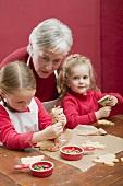 Grossmutter und zwei Enkeltöchter verzieren Weihnachtskekse