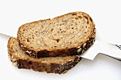 Two slices of multigrain bread with bread knife