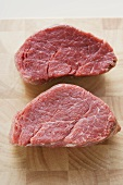 Two beef medallions on chopping board
